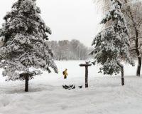 一个救生服的滑雪者在公园跑 免版税库存图片
