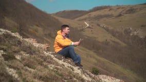 一个救生服的,蓝色牛仔裤一个人在他的手上坐岩石和神色,拿着一张旅客s卡片 股票视频