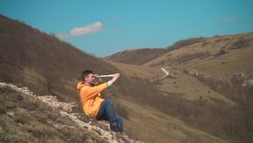 一个救生服的,蓝色牛仔裤一年轻人坐岩石并且调查小望远镜 背景是山和天空 股票录像