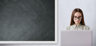 一个教育概念 有长的黑发佩带的玻璃工作的俏丽的女小学生与她的大白色膝上型计算机在教室 免版税图库摄影
