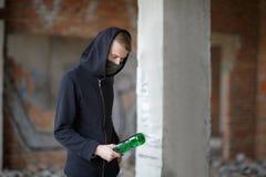 一个敞篷的一个人有一个瓶的在他的手上在一个被放弃的建造场所站立 免版税库存图片