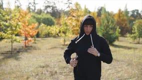 一个敞篷的一名妇女在她的头在秋天公园附近跑自白天 影视素材