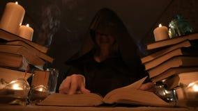 一个敞篷的中等特写镜头女孩魔术师在一个暗室通过烛光和寻找移交书的咒语 低 股票视频