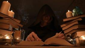 一个敞篷的中等特写镜头女孩魔术师在一个暗室通过烛光和寻找移交书的咒语 低 股票录像