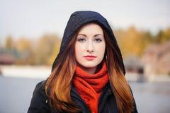 一个敞篷的年轻俏丽的妇女在反对一根黄色森林、红色头发和一条围巾的冷的季节在她的脖子上 免版税图库摄影