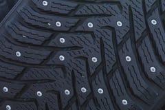 一个散布的轮胎的特写镜头有钉的冬天驾驶的 免版税库存照片