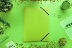 一个文件夹和办公用品的绿色概念在书桌上 免版税图库摄影