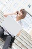 一个断裂的美丽的女实业家与膝上型计算机和电话 免版税库存照片