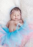 一个新出生的女孩的画象有一根桃红色和蓝色裙子和头发的 免版税图库摄影