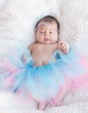 一个新出生的女孩的画象有一根桃红色和蓝色裙子和头发的 库存照片