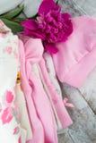 一个新出生的女婴的桃红色初生婴儿用品有peone的 免版税库存图片