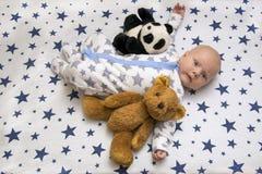 一个新出生的婴孩在有玩具熊和熊猫的,顶视图小儿床在 免版税库存照片