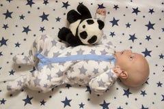 一个新出生的婴孩在有玩具熊猫的,顶视图小儿床在 免版税库存图片