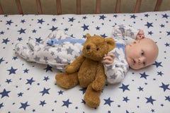 一个新出生的婴孩在有玩具熊的,顶视图小儿床在 免版税库存照片