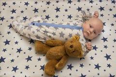 一个新出生的婴孩在有玩具熊的,顶视图小儿床在 免版税库存图片