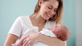 一个新出生的婴孩是在母亲` s胳膊 子项她的妈妈 日花产生母亲妈咪儿子 轻轻地抚摸她的孩子头  慢 股票录像