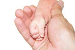 一个新出生的婴孩的手在一个年轻父亲的手上 库存照片