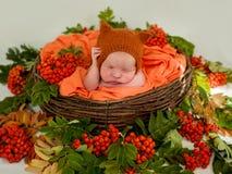 一个新出生的婴孩的画象橙色衣裳的 新出生 免版税库存照片