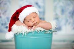 一个新出生的男婴的画象, l佩带的圣诞节帽子,睡觉 图库摄影