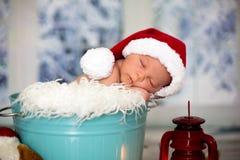 一个新出生的男婴的画象, l佩带的圣诞节帽子,睡觉 免版税图库摄影