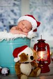 一个新出生的男婴的画象, l佩带的圣诞节帽子,睡觉 免版税库存图片