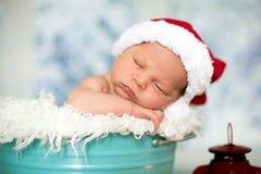 一个新出生的男婴的画象, l佩带的圣诞节帽子,睡觉 库存图片