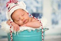 一个新出生的男婴的画象, l佩带的圣诞节帽子,睡觉 免版税库存照片