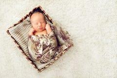 一个新出生的婴孩在一被编织的棕色sca包裹的抽屉睡觉 图库摄影