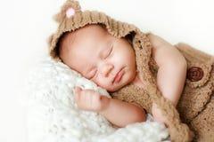 一个新出生的婴孩的照片卷曲了睡觉在毯子 免版税库存图片