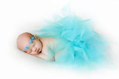 一个新出生的婴孩的照片卷曲了睡觉在毯子 库存照片