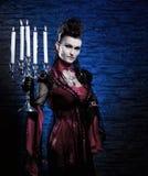 一个新和性感的夫人吸血鬼藏品蜡烛 免版税库存照片