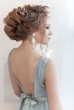 一个新娘一件柔和的蓝色轻的礼服的有大耳环的和装饰物的美好的容量发型在头发 库存图片