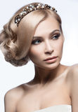 一个新娘的图象的美丽的白肤金发的女孩有一个冠状头饰的在她的头发 秀丽表面 背景镜象婚礼白色 免版税库存图片
