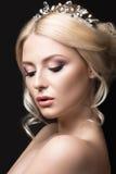 一个新娘的图象的美丽的白肤金发的女孩有一个冠状头饰的在她的头发 秀丽表面 背景镜象婚礼白色 免版税库存照片