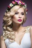 一个新娘的图象的美丽的白肤金发的女孩有花的在她的头发 秀丽表面 背景镜象婚礼白色 免版税库存图片