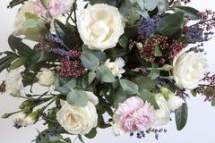 一个新娘的婚礼花束从玫瑰,一支桃红色康乃馨,在一张木桌上的玉树的 库存照片