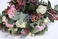 一个新娘的婚礼花束从玫瑰,一支桃红色康乃馨,在一张木桌上的玉树的 图库摄影
