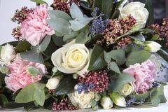 一个新娘的婚礼花束从玫瑰,一支桃红色康乃馨,在一张木桌上的玉树的 免版税图库摄影
