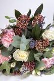 一个新娘的婚礼花束从玫瑰,一支桃红色康乃馨,在一张木桌上的玉树的 免版税库存图片