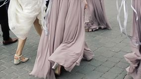 一个新娘的特写镜头白色长的庄重装束的走在沥青的礼服和三个女傧相的 股票视频