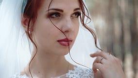 一个新娘的画象在一个森林里,接触她的头发,特写镜头,慢动作卷毛的婚纱的 股票录像