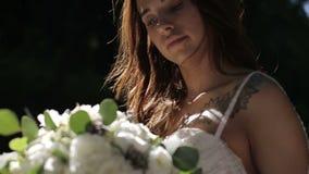 一个新娘的画象婚礼礼服的与花在一个晴朗的公园 股票录像
