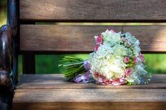 一个新娘的花束一条白色长凳的 美好的花束婚礼 免版税库存图片