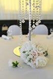 一个新娘的花束从白玫瑰和牡丹的和新郎` s钮扣眼上插的花在一张装饰的桌上说谎 免版税库存图片