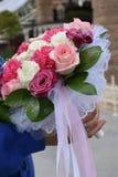 一个新娘的花束从白色和桃红色玫瑰的在妇女的手上 库存照片