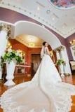 一个新娘的画象一件礼服的有一列长的火车的 免版税库存图片