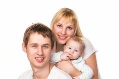 一个新愉快的系列的纵向: 母亲、父亲和婴孩微笑 免版税库存图片