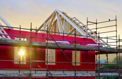一个新房建设中有红色防护层数、脚手架和木材的 免版税图库摄影