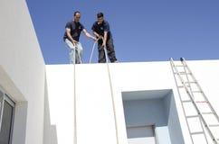一个新房的屋顶的两名工作者有绳索和梯子的Mitzpe拉蒙,以色列 免版税图库摄影