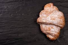 一个新月形面包洒与在黑石背景的搽粉的糖与您的文本的拷贝空间 顶视图 库存图片